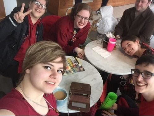 People sitting at tables in a cafe smiling and posing for a group selfie.