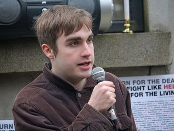 A white person holding and speaking into a microphone. Behind is a stone monument with posters attached.